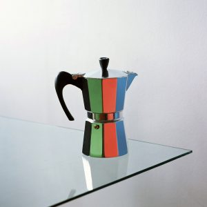 Moka pot reflecting green, red and blue paper